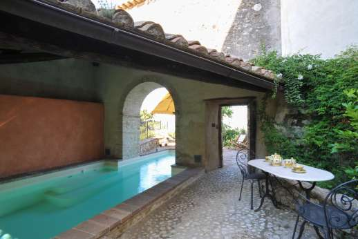 Santi Terzi - Pool partially sheltered by a colonnade, the eastern facade of the palazzo faces into the village through a gated cobblestone courtyard.
