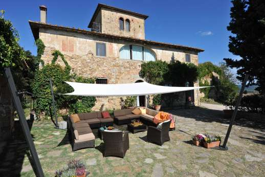 Tizzano - Large paved courtyard with shaded seating area.