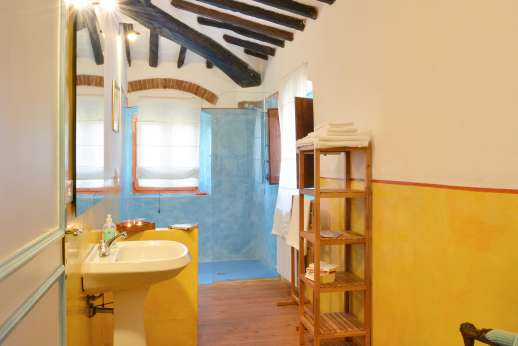 Tizzano - Spacious wall shower in this beamed-ceiling en suite bathroom.