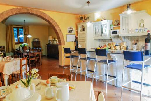 Villa D'Elsa - The kitchen with an archway leading to the open plan dining sitting room.