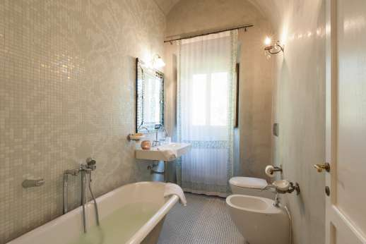 Villa Di Masseto - Bathroom with bath and beautiful white mosaics.