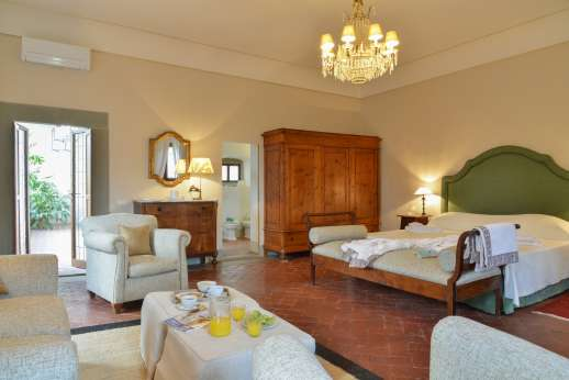 Weddings at Villa Di Masseto - Double bedroom with sofas and antique furniture.