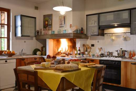 Villa Doveri - A well-equipped kitchen with a breakfast table and fireplace.