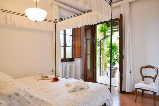 Villa Giotto - Ground floor air conditioned double bedroom with doors leading outside.