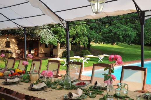 Weddings at Villa Lungomonte - A long shaded dining table for 26 stands by the pool.