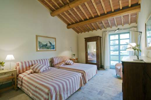 Villa La Leccina Casamora - Air conditioned twin bedroom, with an en suite bathroom with bath.