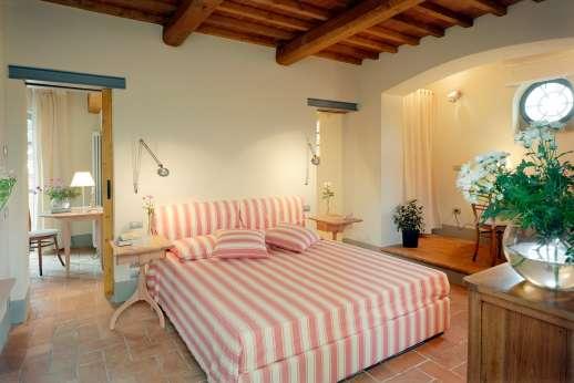 Villa La Nocciolina Casamora - Air conditioned double bedroom with an en suite bathroom with bath, doors open to the garden.