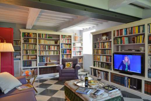 Villa le Cipressae - Ground floor sitting room with a library and tv area leading out into the garden.