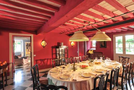 Villa le Cipressae -  Large dining room with an open fireplace leading out into the garden.