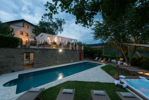 Villa Albizi - The villa and pool in the evening with the door open to the pool house with sauna, gym, shower and toilet.