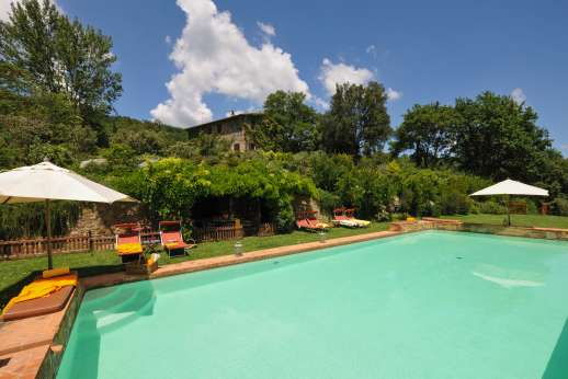 Podere Uccella - The large swimming pool set within a fenced off area with a loggia and pool house with a small gym, WC