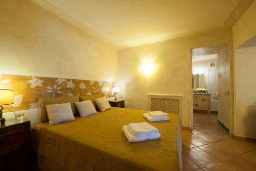 Ciclopica - Lower ground floor double bedroom with sofa, big TV and ensuite bathroom