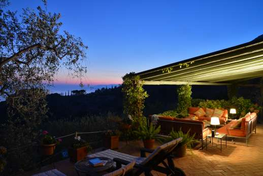 Passo Reo - The outside seating area by the main house with lighting at sunset