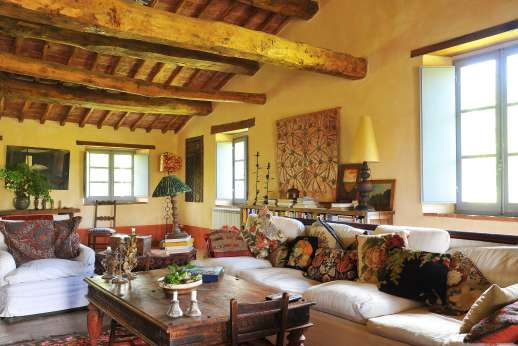 The Rose Barn - The sitting room with a fireplace and TV leading out to a small terrace